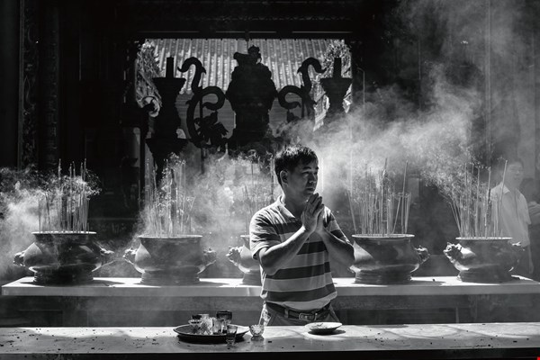 A praying man surrounded by clouds of incense smoke shows just how similar Taiwanese and Vietnamese culture can be.