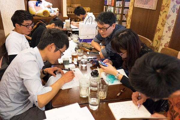 A group of pen enthusiasts enjoy a meetup, chatting and sharing examples of their penmanship.