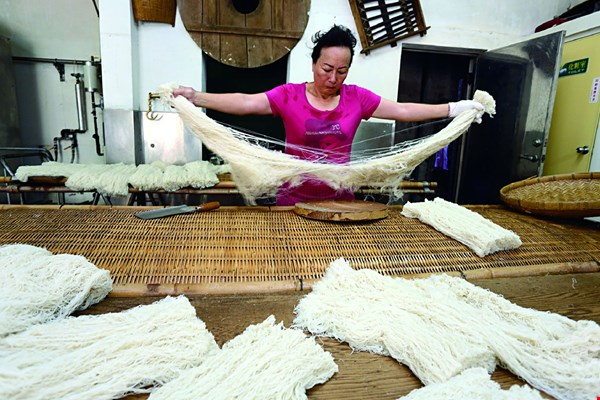 The rice-flour dough is pressed through holes into long skeins, which are placed in steamers before finally being separated to cool. Making dry rice vermicelli is a long, involved process.