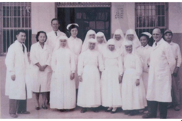 The pioneering staff of St. Joseph's Hospital in its early days. Father Georges Massin stands on the right wearing a lab coat. (courtesy of St. Joseph's Hospital)