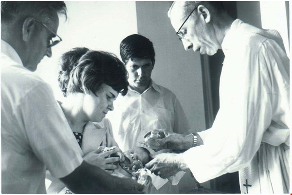 Father Antione Pierrot baptizes the child of a German teacher (center) at Yongnian Middle School. (courtesy of St. Joseph's Hospital)
