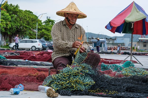 A fisherman with a weathered face deftly repairs a net beside the harbor.  (photo by Chuang Kung-ju)