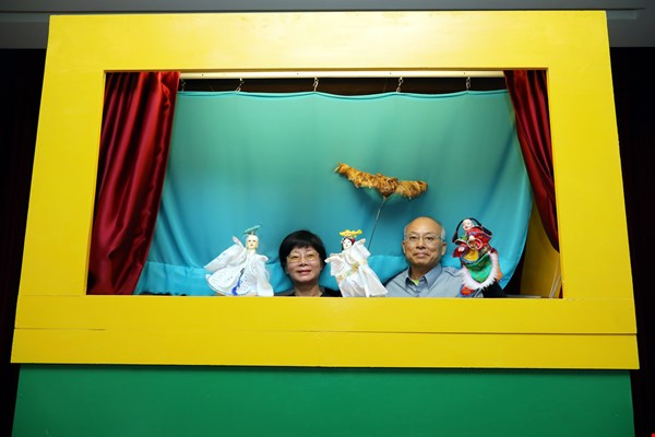 Lin Fen-in (left), who wrote the script for the Ah Gui story, and volunteer performer Li Chin-chu (right), bring life to puppet theater. (photo by Jimmy Lin)