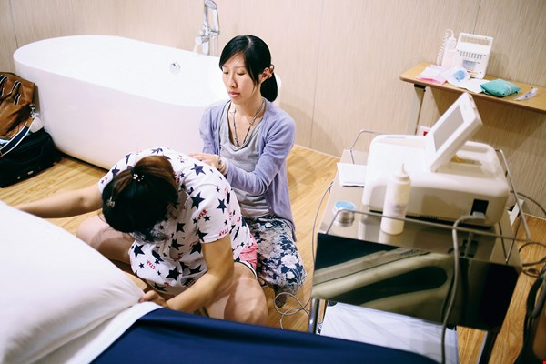 A midwife performs a pelvic massage to reduce pain during contractions and facilitate a smooth delivery. (courtesy of Fish Yu)
