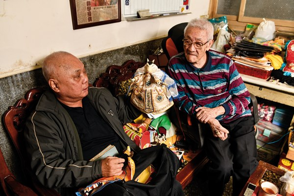 Xu Zhengzong (left), director of the Hsin Hsi Yuan Puppet Theater, often drops by Chen Hsi-huang's home for visits. The two often chat about the old days, including the bygone heyday of glove puppetry.