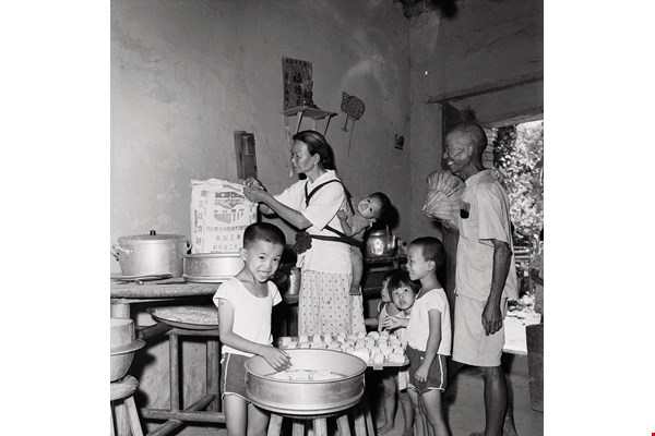 Children look on as their mom transforms wheat flour distributed as part of US aid into noodles and steamed buns. The sense of delight expressed on their faces, as if they were observing a magic trick, is a shared memory for many who lived through that era. (courtesy of the Council of Agriculture)