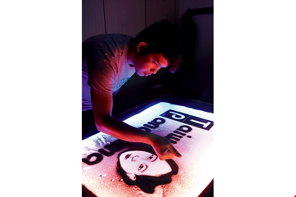 Mario is able to create sand-art text or images precisely according to clients' wishes.