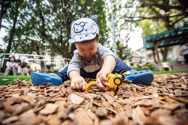 A playground's carpet of woodchips offers children a medium through which to come into contact with nature.