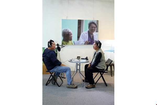 Dr. Hsu (right) chats with Taitung artist Iming Mavaliw on his radio show, part of his regular talks on the air with his supporters.
