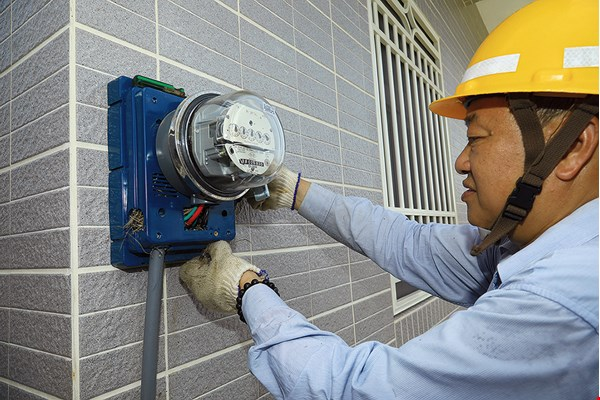 Above, a Taipower employee installs an electricity meter at a new house in Qimei's Haifeng Community. At right, a worker checks on the operation of a diesel generator.
