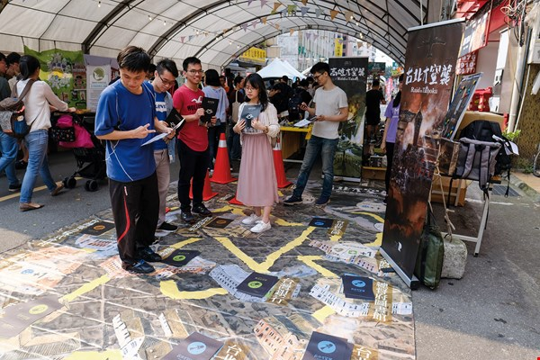 Publishers arrange trial play sessions at exhibitions, drawing in prospective players. Here we see people trying out a blown-up version of the game Raid on Taihoku.