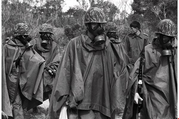 Recruits wear rain ponchos and gas masks for a training exercise involving a simulated chemical attack. (photo by Hang Dah-parng)