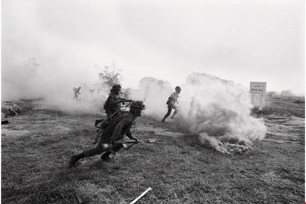 During combat training, soldiers with fixed bayonets throw smoke bombs as they practice storming an enemy position.  (photo by Hang Dah-parng)