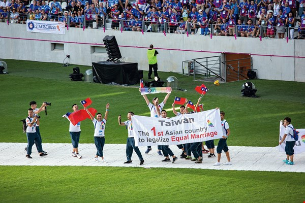 "Taiwan competed in the Paris Gay Games and was supported by countries around the world. The photo shows the team entering the arena, waving national flags and holding up a banner that reads: ""Taiwan: The 1st Asian country to legalize Equal Marriage."" (courtesy of the Taiwan Gay Sports and Taiwan Gay Development Movement Association)"