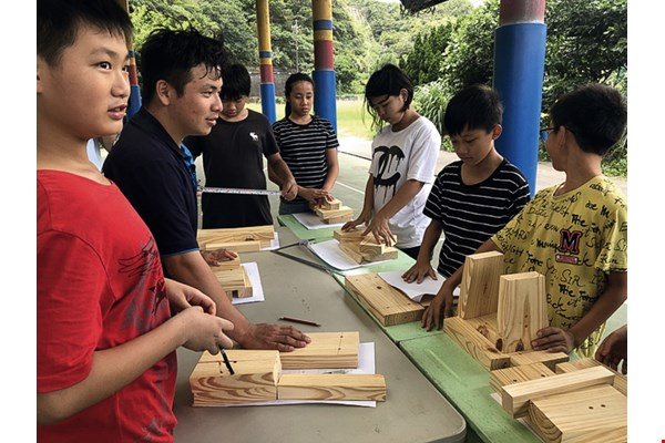 Huang Wei-xiang leads team members from international skills competitions into a primary school where they teach students to make wooden stools, showing that vocational skills can change society.